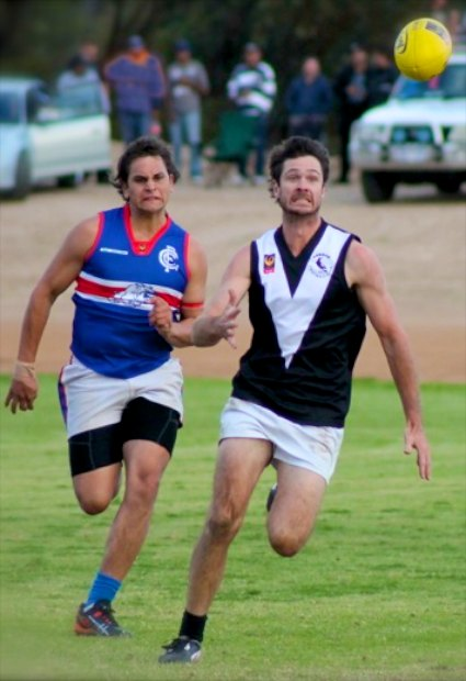Two Australian rules football players chasing a ball.